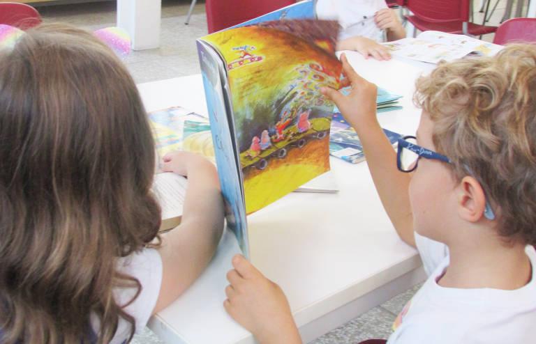 Duas crianças lendo livro em aula na Escola Viva