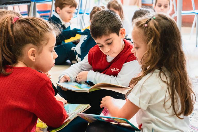 Três crianças pequenas lendo livros