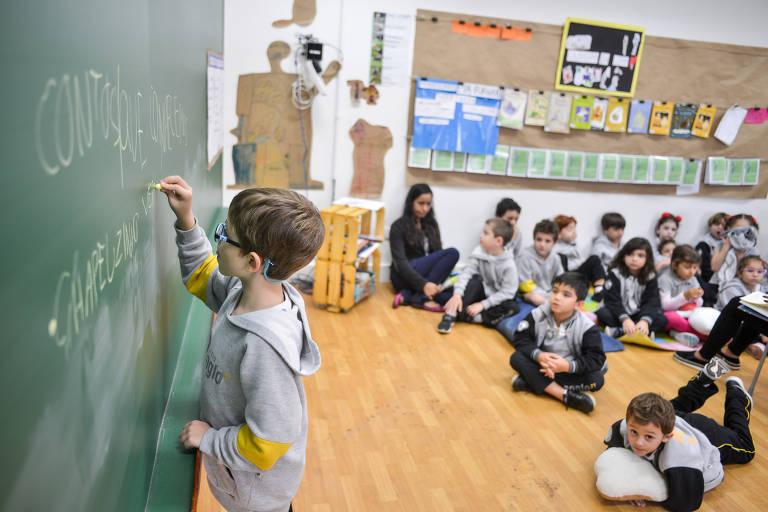 Criança escrevendo em lousa