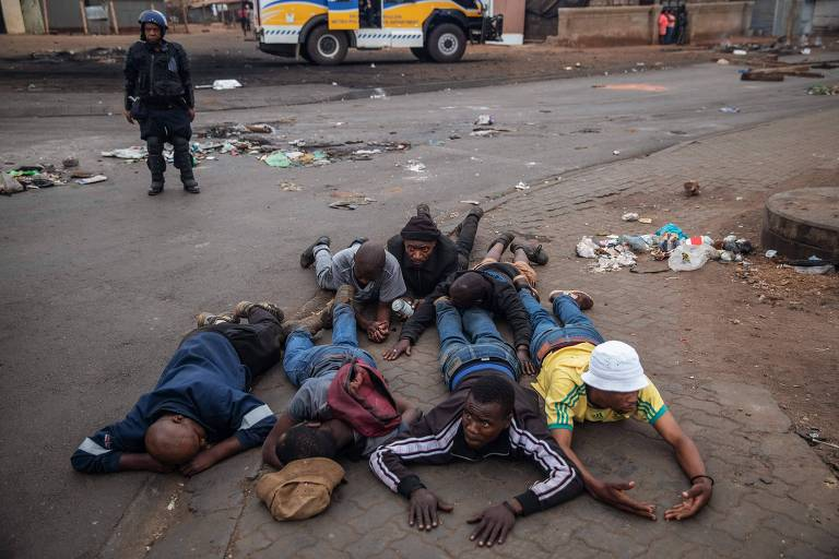 seis pessoas negras deitadas de bruços no chão da rua; policial vestido com equipamento de segurança ao fundo