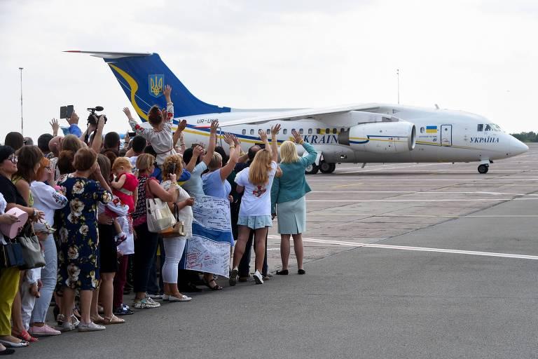 Um avião aterrissa no aeroporto enquanto um grupo de pessoas acena em sua direção.