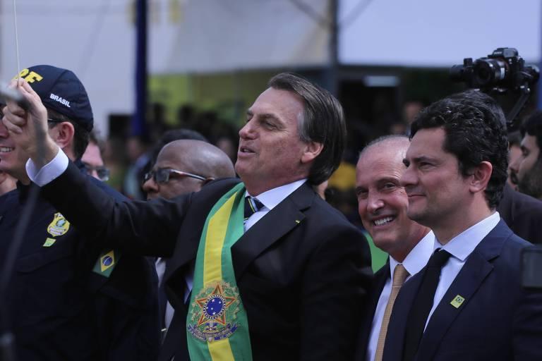 O presidente Jair Bolsonaro sacode um bastão fingindo reger a banda do exército.