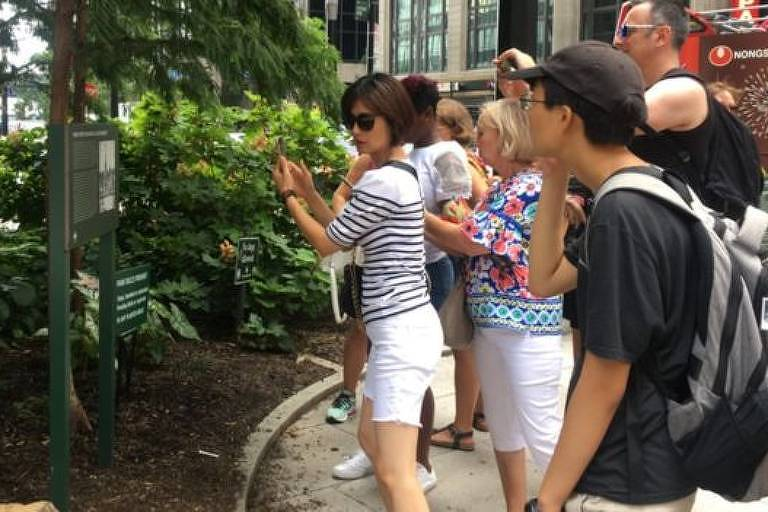 Turistas se reúnem em frente a placa e tiram fotos.