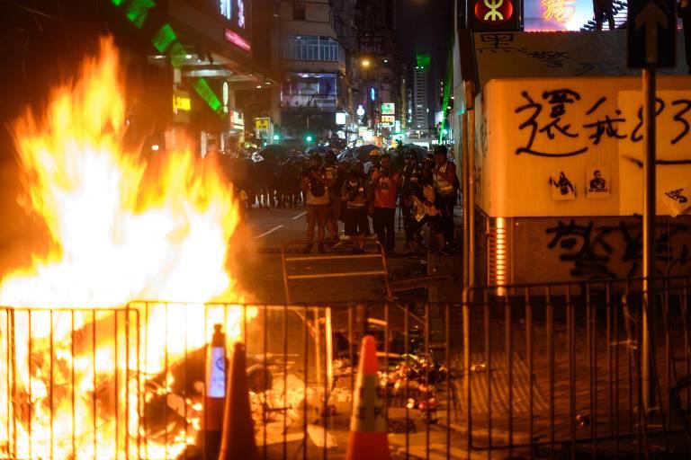 Manifestante ateia fogo em barricada durante protestos no distrito de Mong Kok, em Hong Kong