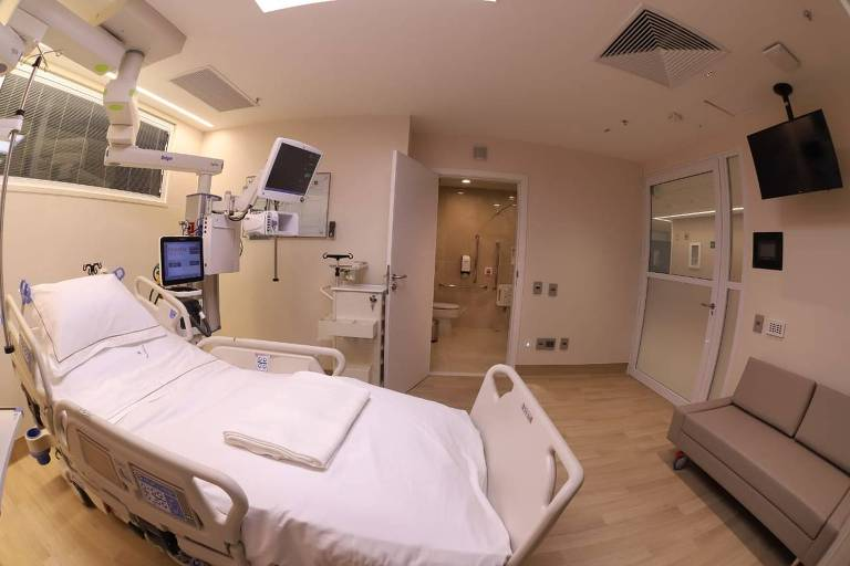 O quarto hospitalar tem televisão, sofá e um leito.