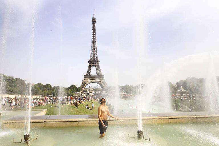 Em frente à Torre Eiffel, homem mergulha na fonte, localizada no parque em torno do monumento, para escapar do  calor intenso