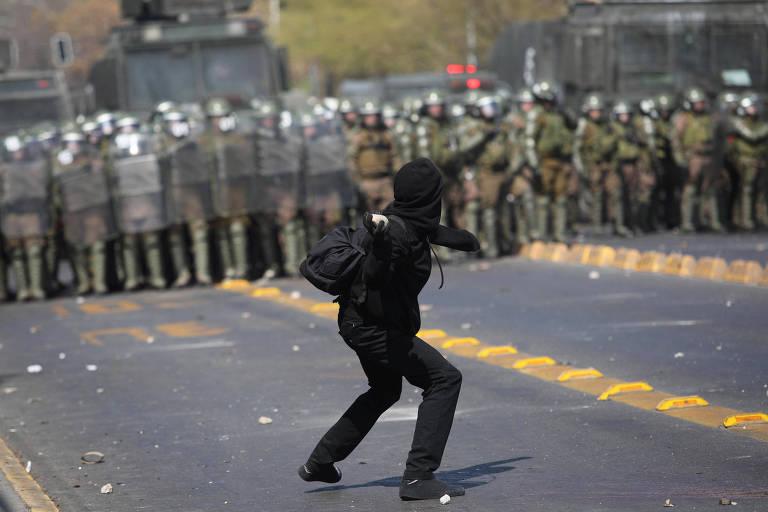 Manifestante atira pedra em policiais durante marcha em memória aos 46 anos do golpe de Estado de 1973 que deu início à ditadura de Augusto Pinochet no Chile