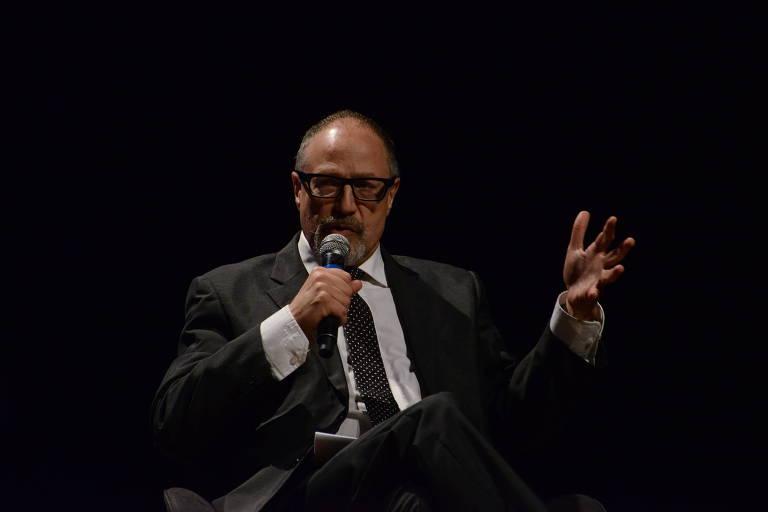Pierre Levy, de terno, fala e gesticula com as mãos