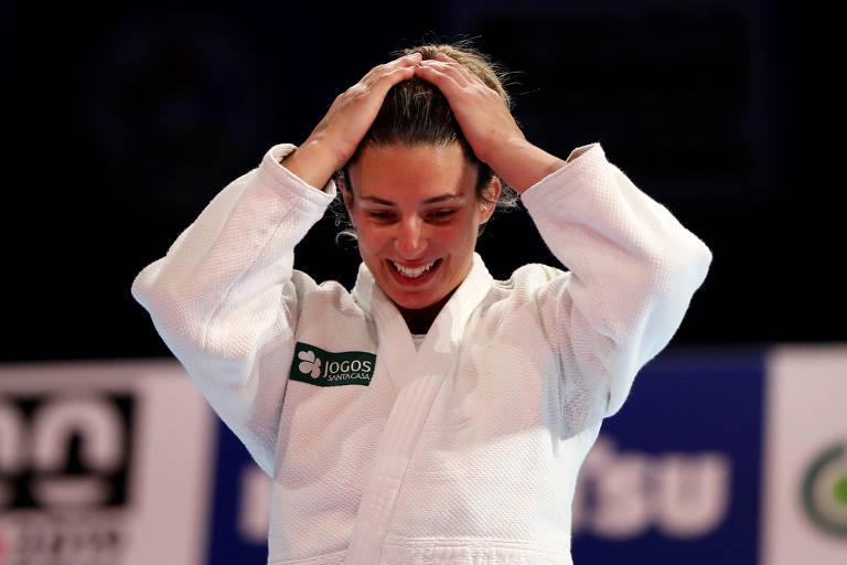 Bárbara Timo sorri e leva as mãos à cabeça