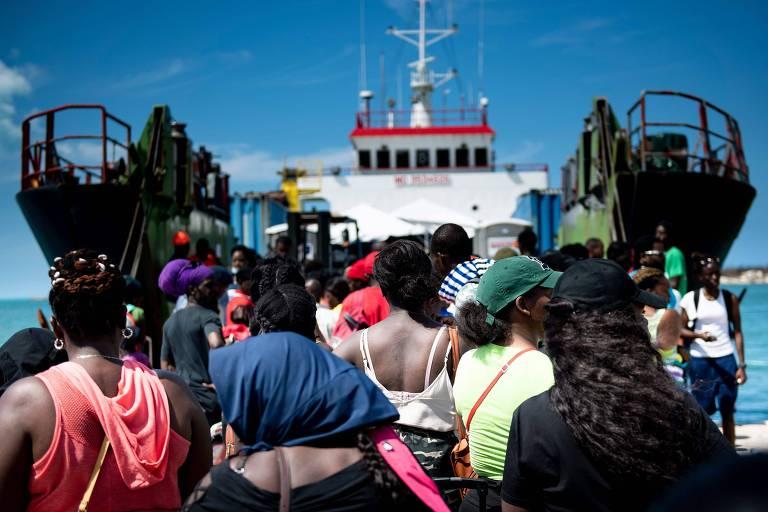 Bahamenses fazem fila para embarcar em um navio de carga