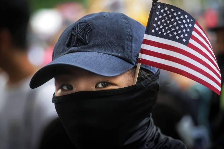 Manifestante com a bandeira americana em Hong Kong em frente à embaixada dos EUA