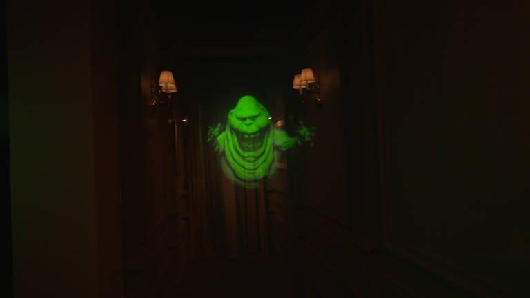 Fantasma aparece iluminado em verde no meio de corredor escuro