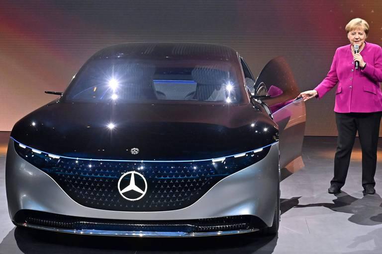 Angela Merkel, com blusa rosa e calça preta, segura microfone enquanto abre porta de carro da Mercedes