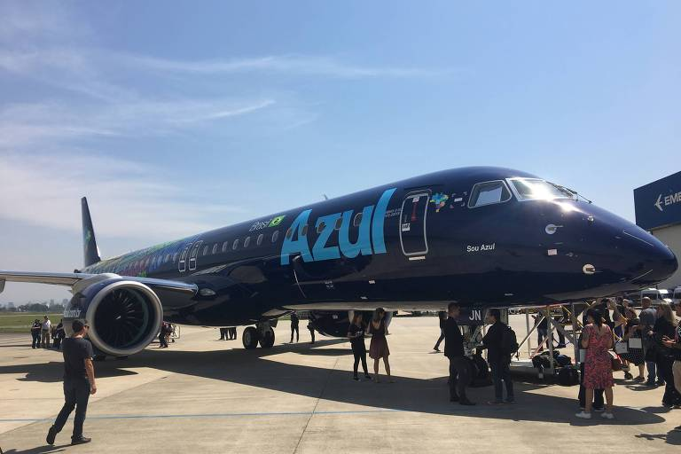 Na foto, o novo avião aparece em primeiro plano, com várias pessoas ao redor. O avião é azul marinho e tem o logo da Azul na lateral