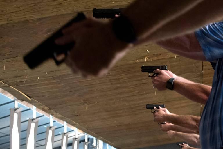mãos seguram armas enfileiradas