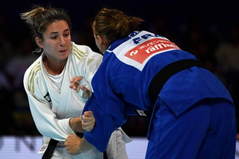 As judocas seguram o quimono da oponente