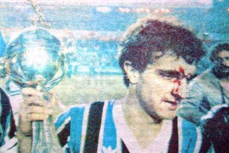 O gremista Tita, com o rosto sangrando, carrega a taça da Libertadores de 1983