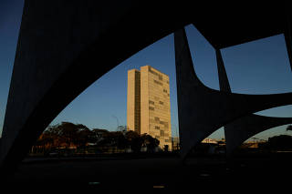 FILE PHOTO: National Congress building can be seen near the columns of the Planalto Palace building during sunrise in Brasilia