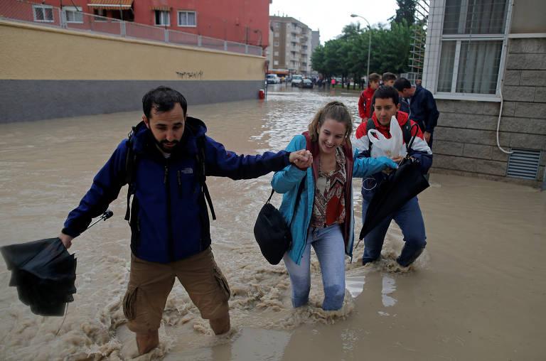 Pessoas dão as mãos para atravessar rua inundada