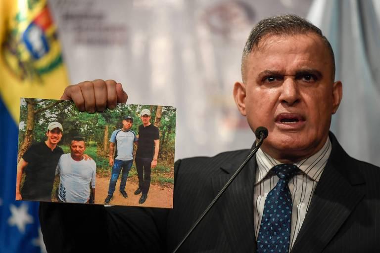 O advogado-geral da Venezuela, o chavista Tarek William Saab, mostra as imagens de Guaidó durante entrevista coletiva nesta sexta (13)