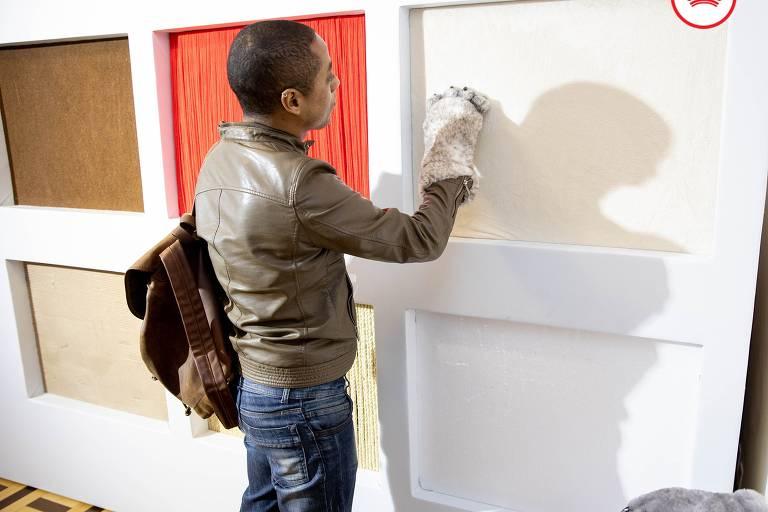 Com uma luva que imita a mão de um gato, homem arranha uma parede com diferentes texturas
