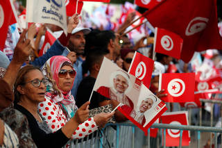 Supporters of presidential candidate Abdelfattah Mourou, hold Tunisian flags and pictures depicting him during his election campaign in Tunis