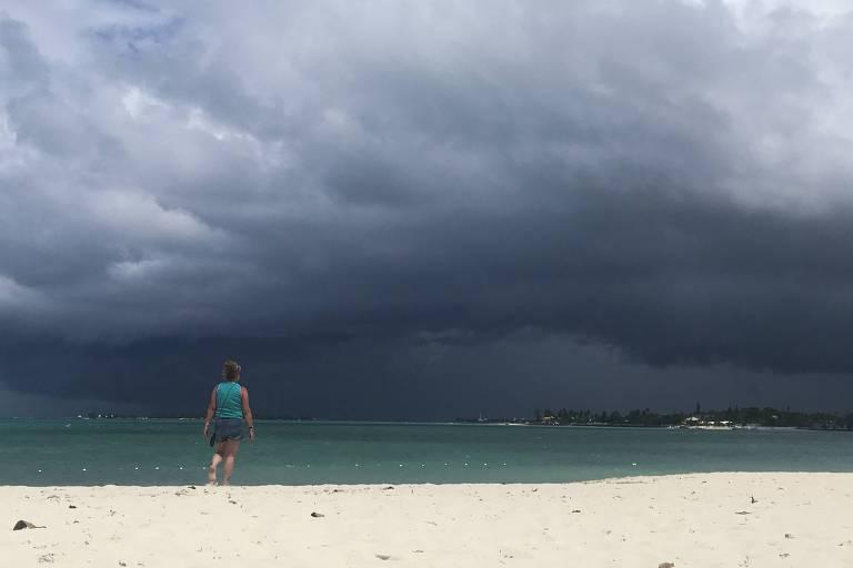 Uma mulher de shorts e camiseta está em pé na beira do mar, em uma praia de areias muito brancas. No mar, no horizonte, o céu está escuro, com nuvens carregadas, com a aproximação da tempestade Humberto.