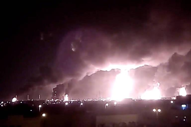 Em meio a noite, uma bola de fogo ilumina o centro da paisagem e é pela própria luminosidade das chamas que se percebe as densas nuvens de fumaça indo em direção ao céu.