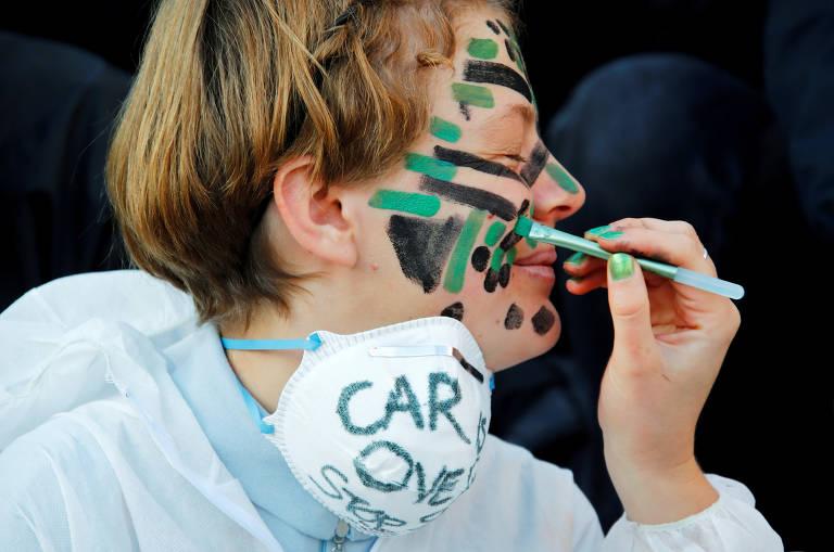 Menino de perfil sorri ao ter o rosto pintado com tintas preta e verde