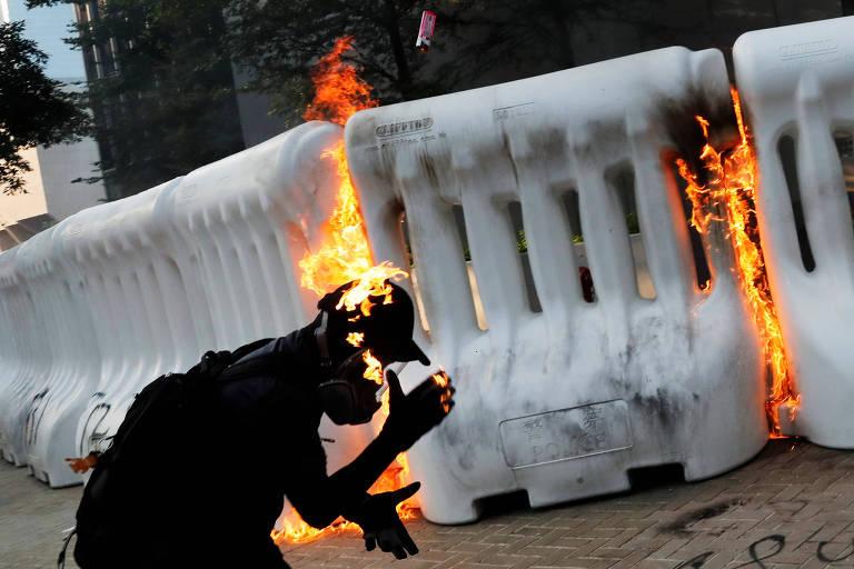 Manifestante em meio a chamas após atirar coquetel molotov durante protesto na região central de Hong Kong