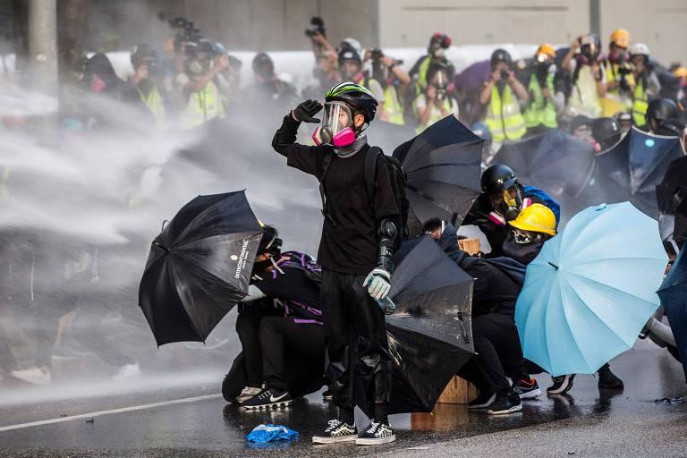 Manifestantes pró-democracia reagem no momento em que a polícia usa jatos de água contra eles