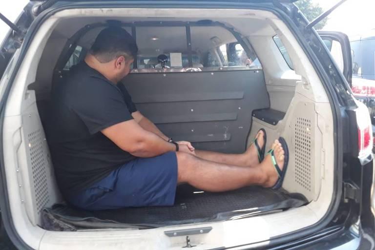 André de Oliveira Macedo, o André do Rap, no carro da Polícia Civil  após chegar do Rio