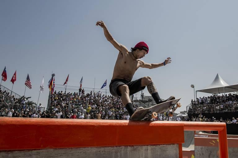 Homem sem camisa com skate sobre uma barra