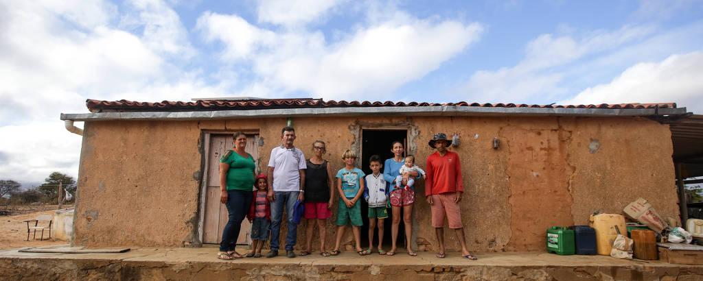 Família com crianças e adultos enfileirada em frente à casa no sertão