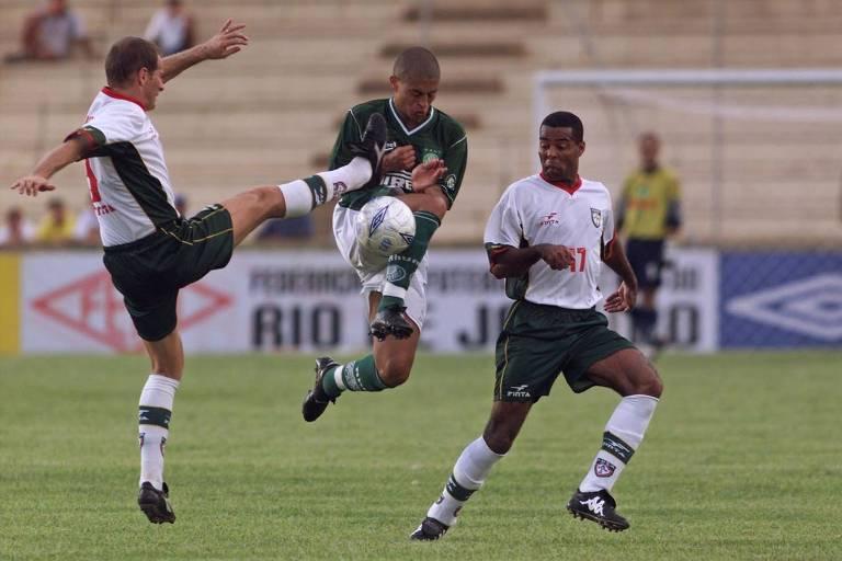 O meia palmeirense Alex sofre falta de jogador da Portuguesa durante partida no estádio Benedito Teixeira, em São José do Rio Preto