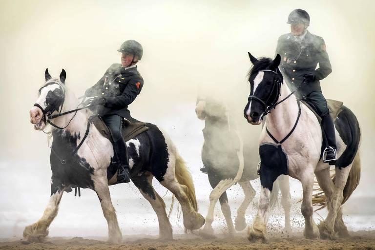 Dois homens fardados montam em cavalos nas cores branco e preto. Os animais estão em movimento