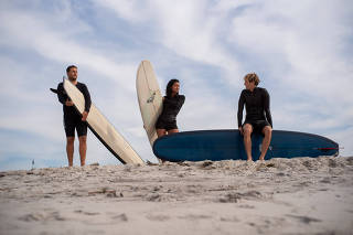 Long board surfers Justin Quintal, Kelia Moniz and Harrison Roach practice at Long Beach, on Long Island in New York, Sept. 5, 2019. (Todd Heisler/The New York Times)