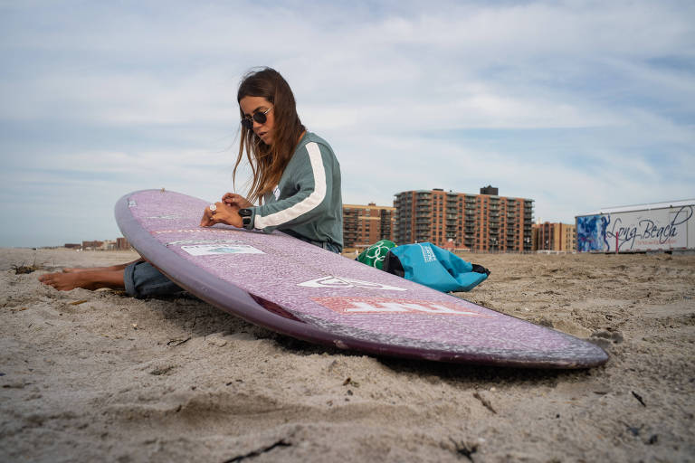 A brasileira Chloe Calmon prepara sua prancha de longboard em Long Beach