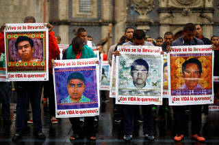 Students hold portraits of the 43 missing Ayotzinapa College Raul Isidro Burgos students during a march to mark the 35 months since their disappearance in the state of Guerrero, in Mexico City