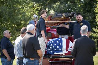 Joe Heller?s coffin is carried on the Essex Fire Department?s 1941 Mack firetruck that Heller helped restore, in Essex, Conn., Sept. 13, 2019. (Monica Jorge/The New York Times)