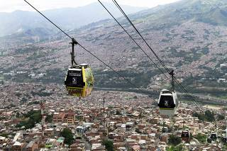 Cable cars pass above the town of Medellin