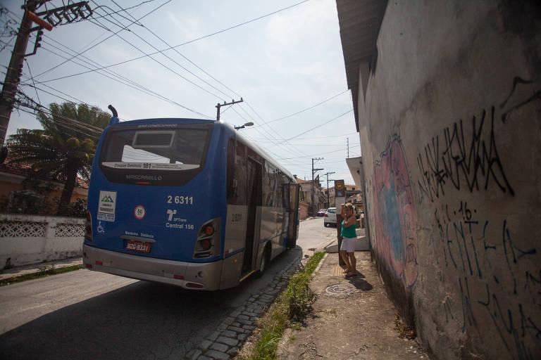 Iara Maria de Arruda Campos Garcia no ponto de ônibus que, segundo a leitora, está instalado no local errado; ela relata que já ocorreram acidentes
