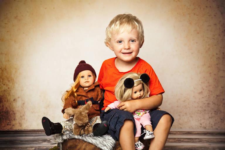 Menino loiro sentado, de camiseta laranja, sorri e segura duas bonecas