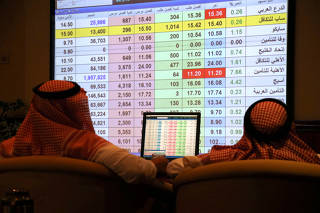 Saudi men inspect a screen showing stock prices at ANB Bank in Riyadh