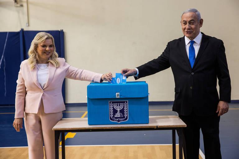 Duas pessoas depositam bilhete em urna