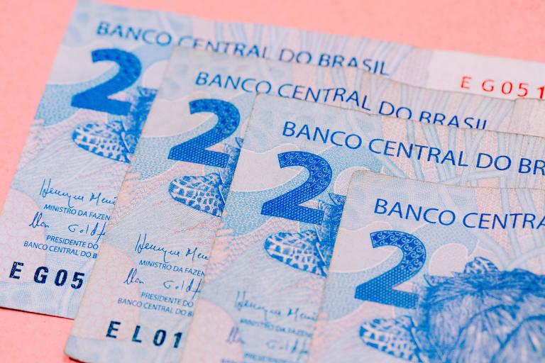 Notas de R$ 2 sobrepostas em mesa rosa