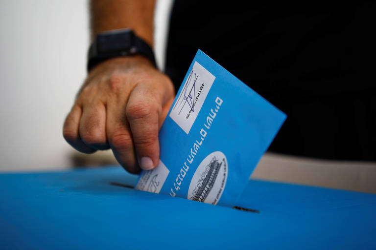 Voto sendo colocado em urna em uma zona eleitoral de Tel Aviv