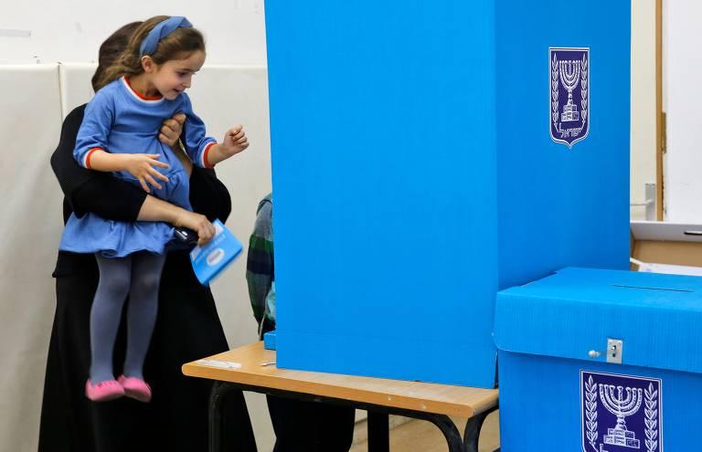 Judia ultra-ortodoxa carrega filha enquanto se prepara para votar em Tel Aviv