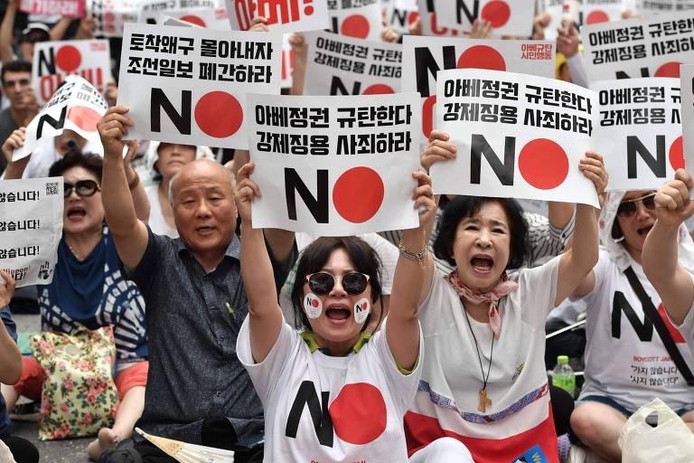 Manifestantes em Seul com cartazes contrários ao Japão