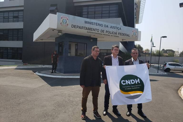 Em frente ao prédio da Superintendência Regional do Paraná, três homens, todos vestidos com camisa, casaco, calça e sapatos sociais, carregam uma bandeira branca em que se lê CNDH - Conselho Nacional de Direitos Humanos. Os escritos estão dentro de um círculo verde e amarelo.